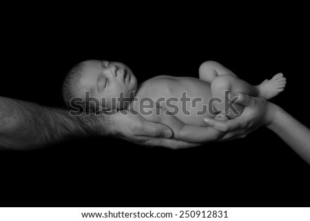 Sleeping newborn baby in her arms mom and dad. Concept of love, protection of children. Studio, black background. black and white photography - stock photo