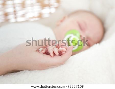 Sleeping newborn baby. Mother's hand holds infant's hand. - stock photo