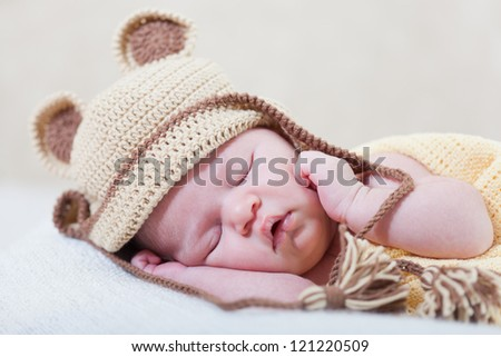 sleeping newborn baby with a ridiculous knitted hat - stock photo