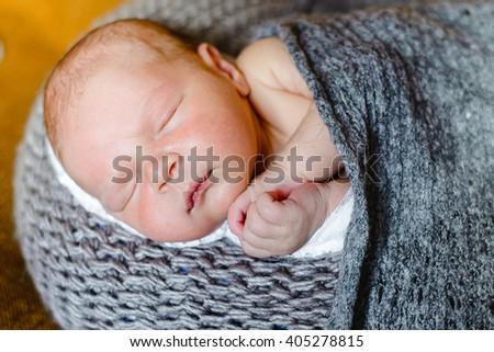 sleeping newborn baby wrapped in a blanket.  Newborn baby boy - stock photo