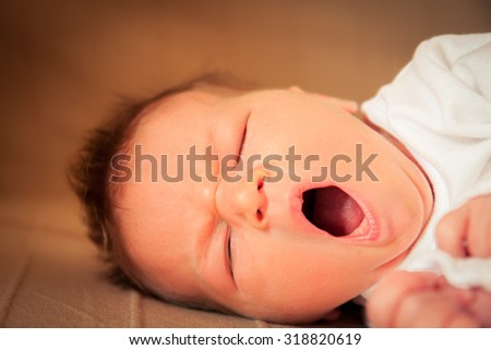Sleeping newborn baby yawning - stock photo