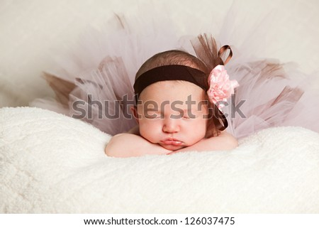 Sleeping newborn dressed in a headband and tutu. - stock photo