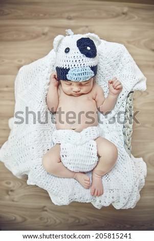Sleeping newborn in basket over delicate pink background - stock photo