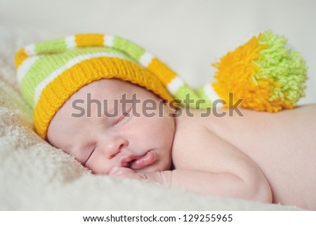 sleeping newborn wearing funny hat - stock photo