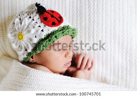 Sleeping newborn wearing knitted hat - stock photo