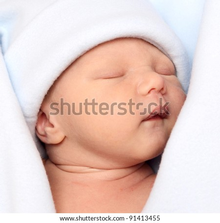 sleeping smiling newborn baby on blanket