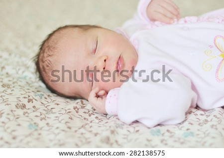 sleeping sweet newborn girl on the bed - stock photo