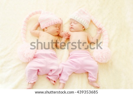 sleeping twins wearing funny hats with big pompoms