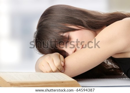 Sleeping while learning - tired teen woman sleeping on desk - stock photo