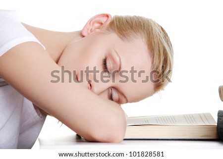 Sleeping while learning - tired teen woman sleeping on desk. Isolated on white background - stock photo