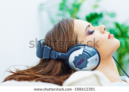 Sleeping woman at home with headphones, listening music. - stock photo