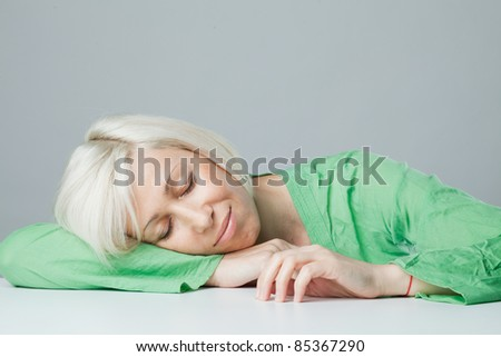 sleeping woman in a green robe over his head tucked under the table hands