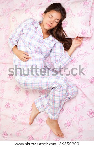 Sleeping woman in bed having beauty sleep in pajamas. Beautiful cute girl in her twenties. Asian Caucasian female model in full length lying down. High angle view.