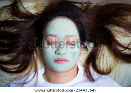sleeping woman in clay mud facial mask on face at night , girl taking care of dry complexion. beauty treatment - stock photo