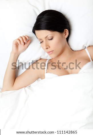 Sleeping woman in the queensize bed, white background - stock photo