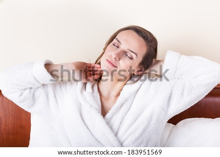 Sleeping woman in white bathrobe in bed - stock photo