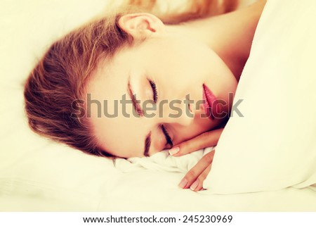 Sleeping woman lying in bed at home. - stock photo