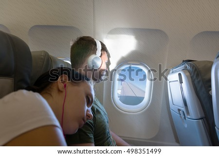 Sleeping woman lying on the male shoulder while he looking out the window of an flying airplane