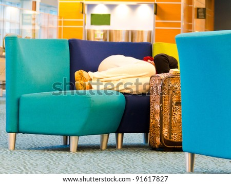 Sleeping woman (passenger) in the airport terminal  in anticipation of departure (landing) of an aircraft (or any transport). Flight delay due to weather or strike. - stock photo