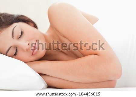 Sleeping woman resting her head on the pillow. A close up view of the woman. - stock photo