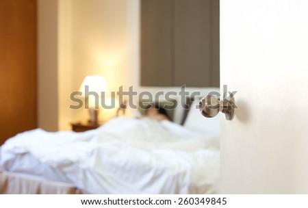 sleeping woman resting in bed with door open - stock photo