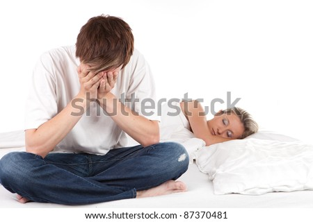 Sleeping woman, while her boyfriend is sitting on a disturbing edge of the bed - stock photo