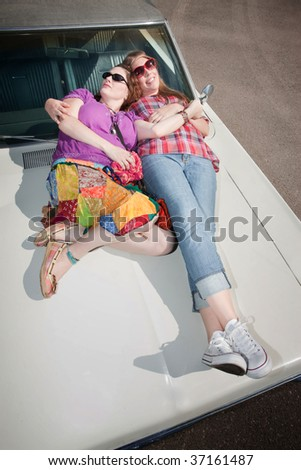 Sleeping women on an old car hood - stock photo