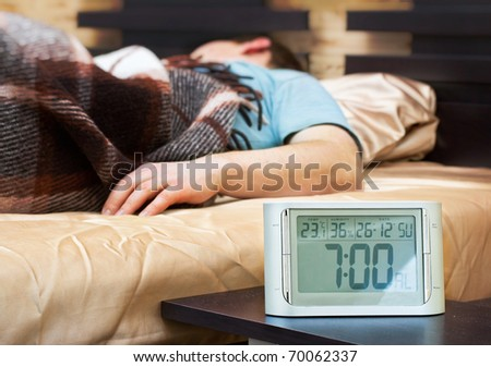 Sleeping young man with alarm clock at foreground - stock photo