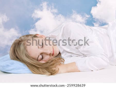 Sleeping young woman on the sky background. - stock photo