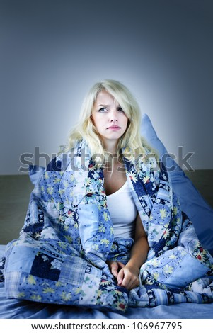 Sleepless blonde woman in bed with insomnia - stock photo