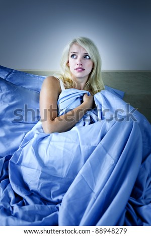 Sleepless blonde woman scared at night in bed - stock photo