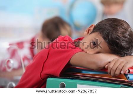 sleepy boy in classroom - stock photo