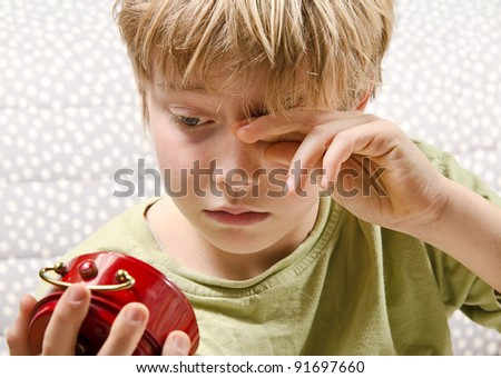sleepy boy wondering about the actual morning time - stock photo