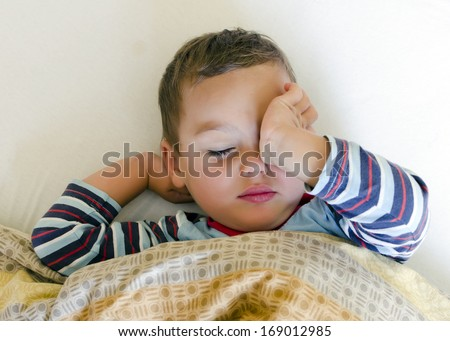 Sleepy child in the bed waking up or getting sleep.  - stock photo
