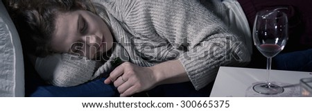 Sleepy drunk woman on couch with bottle of wine - stock photo