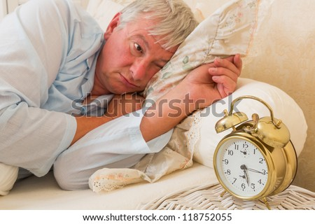 Sleepy elderly man waking up and looking at the alarm clock with one eye - focus is on the alarm clock - stock photo