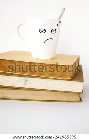 sleepy face coffee cup on stack of old books - stock photo