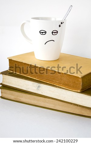 sleepy face coffee cup on stack of text books - stock photo