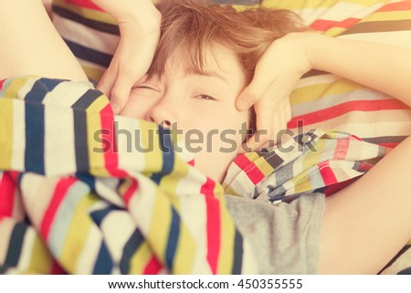 Sleepy girl teenager lying in bed under a striped colored blanket. Toned - stock photo