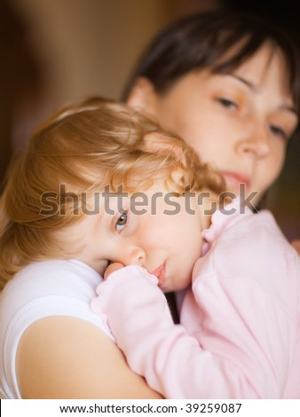 Sleepy little child with mom - shallow DOF, focus on little girl's eyes - stock photo