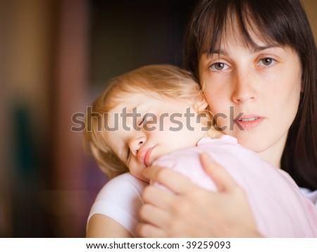 Sleepy little child with mom - shallow DOF, focus on woman's eyes - stock photo