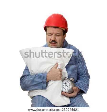 Sleepy male in red protective helmet on his head sits hugging pillow and hold an alarm clock in hand isolated on white background. Protection against insomnia concept - stock photo