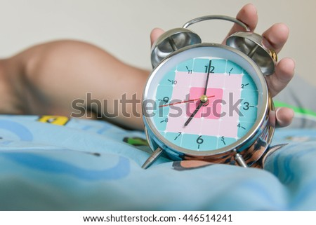 sleepy man is expanding hand to stop the alarm clock that showing time for 7 AM - stock photo