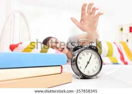 Sleepy man reaching for the alarm clock seeping on a bed at home - stock photo