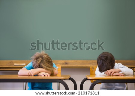 Sleepy pupils napping at desks in classroom at the elementary school - stock photo