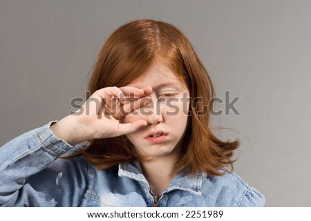 Sleepy read-haired young girl rubs her eyes