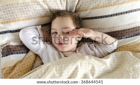 Sleepy sick or ill child lying in a bed, waking up in the morning.