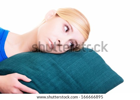 Sleepy tired blond girl with green pillow almost falling asleep. Young teen woman female student with lack of sleep isolated over white background