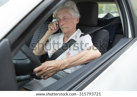 sleepy, tired,  exhausted senior woman  driving her car after long hour trip - stock photo