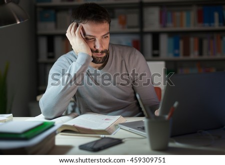 Sleepy tired young man sitting at desk, working and studying late at night, he is leaning on his hand and staring at the laptop screen - stock photo